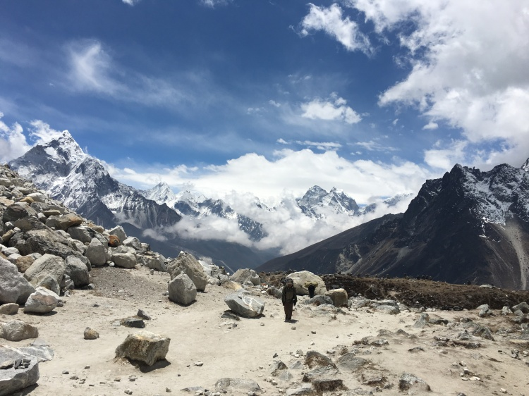 Sherpa in middle of the Himalayan mountains carrying gear as a porter.
